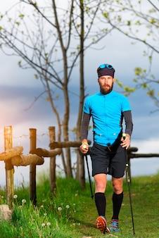 Caminhada nórdica de um homem perto de uma cerca de madeira