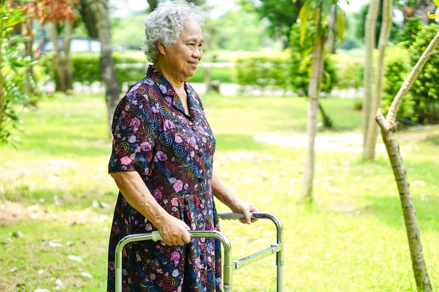 Caminhada paciente asiática ou idosa asiática da senhora idosa com o caminhante no parque.