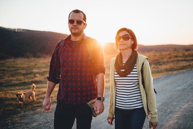 Caminhadas casal com cachorro em uma estrada de terra durante o pôr do sol