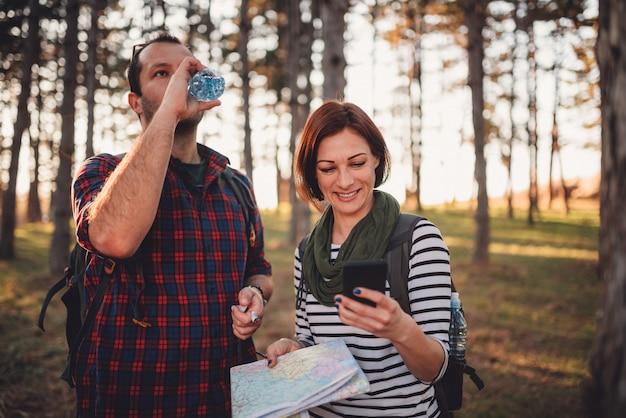Caminhadas casal navegando na floresta usando o mapa e telefone inteligente