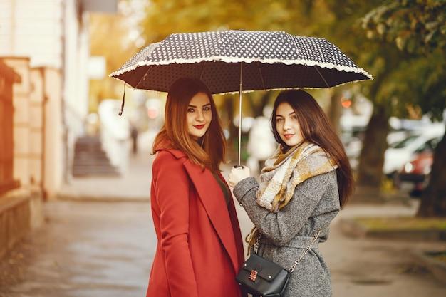 Caminhadas de garotas. mulheres com guarda-chuva. senhora com um casaco.