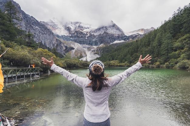 Caminhadas jovem viajante mulher olhando a bela paisagem e refrescante na reserva natural de yading