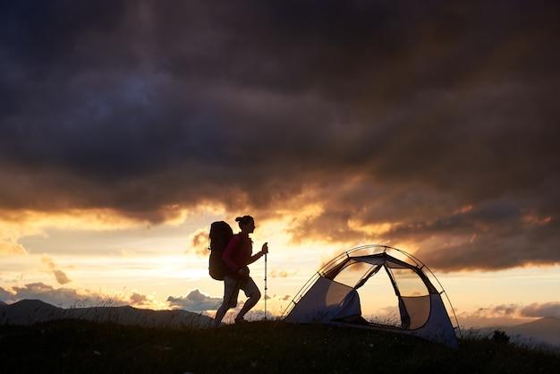 Caminhadas menina perto da tenda, hora do sol nas montanhas da romênia