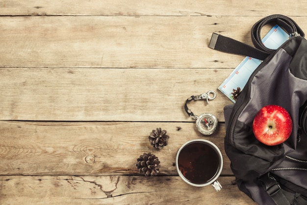 Caminhadas mochila, bússola, cinto e outros equipamentos de camping em uma superfície de madeira. o conceito de caminhadas nas montanhas ou na floresta, turismo, descanso de barraca, acampamento. vista plana leiga, superior.