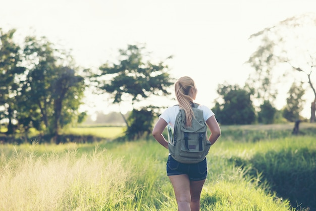 Caminhadas mulher com mochila andando em uma estrada de cascalho