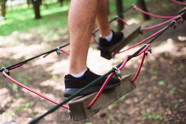 Caminhadas na corda estacionar jovem em equipamento seguro.