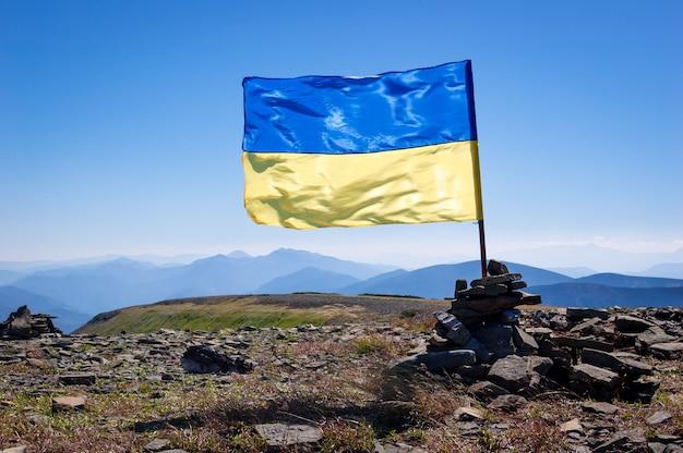 Caminhadas nos cárpatos ucranianos. bandeira da ucrânia no topo da montanha. aventura de verão