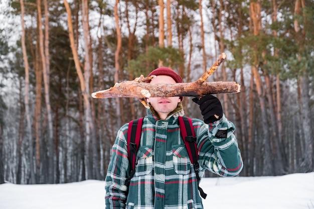Caminhadas pessoa do sexo masculino na floresta de inverno. homem sorridente na camisa quadriculada de inverno mantém um tronco de madeira de pinho