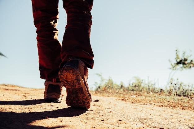 Caminhadas sapatos em ação em um caminho de trilha de deserto de montanha.