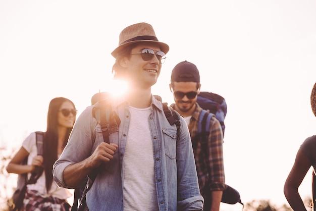 Caminhando de amigos. grupo de jovens com mochilas caminhando juntos e parecendo felizes