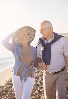 Caminhando em um dia de muito sol. casal idoso na praia, aposentadoria e conceito de férias de verão