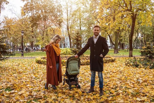 Caminhando em um parque de outono com uma jovem família com um bebê recém-nascido em um carrinho