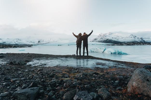 Caminhando em uma geleira na islândia, vista de tirar o fôlego, o viajante fica em pé na pedra, os viajantes chegaram ao seu destino, amizade