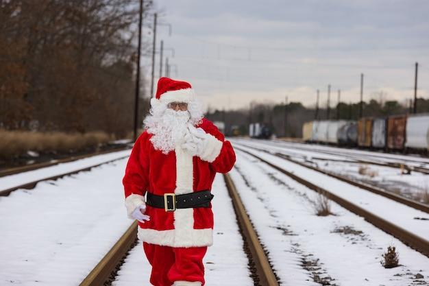 Caminhando na ferrovia, papai noel acena carregando presentes de natal