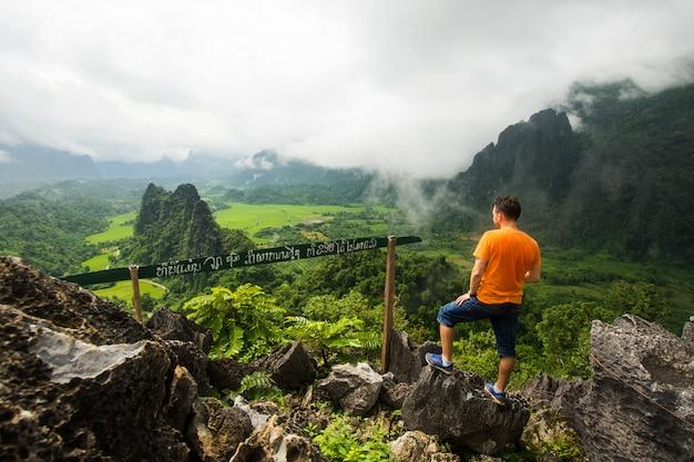 Caminhando o suporte do homem na montanha superior com opinião da natureza.