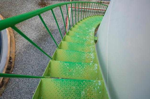 Caminhando pela escada, tanque de armazenamento químico verde