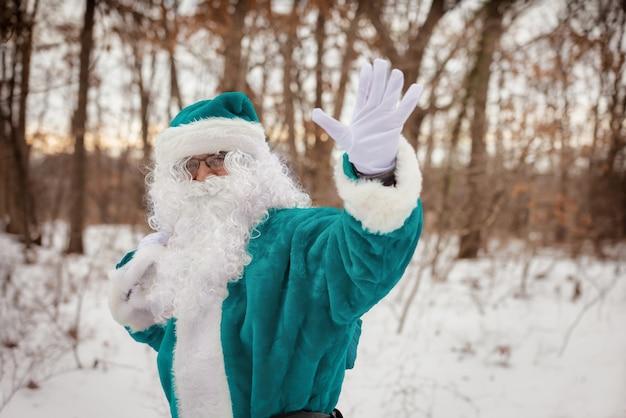 Caminhando pela floresta de inverno, o elfo em um vestido de terno verde acena com a mão carregando presentes de natal