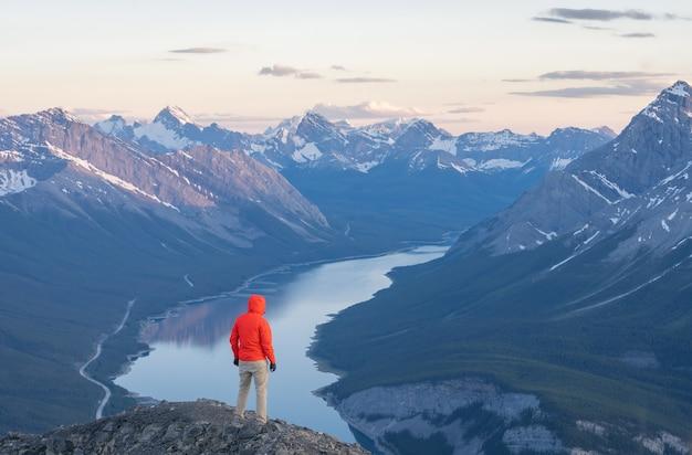 Caminhante apreciando a vista do pôr do sol no cume do rimwall canada no vale alpino