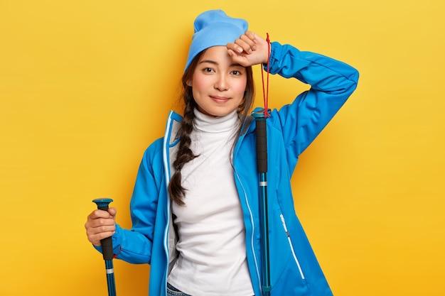 Caminhante asiática cansada posa com bastões de trekking, faz atividades ao ar livre, viaja, vestida de terno azul, toca a testa, olha com expressão calma, isolada sobre a parede amarela
