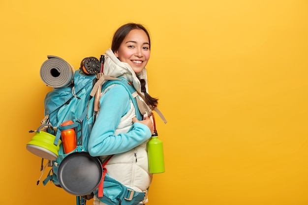 Caminhante asiática positiva fica de lado para a câmera, carrega uma mochila grande com coisas necessárias para a viagem, faz uma viagem de aventura emocionante, isolada sobre a parede amarela