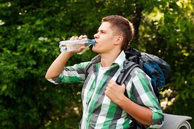 Caminhante bebendo água na floresta