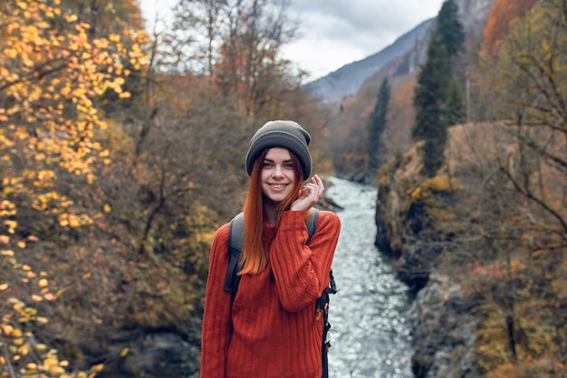 Caminhante bonita com roupas de outono nas montanhas perto da natureza do rio