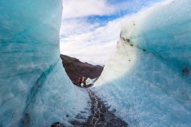 Caminhante caminhando passar parede de gelo durante caminhadas na geleira, solheimajokull