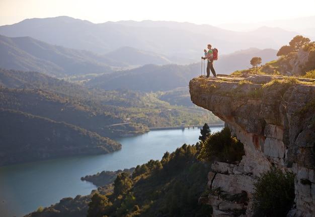 Caminhante com bebê relaxando no penhasco e apreciando a vista do vale