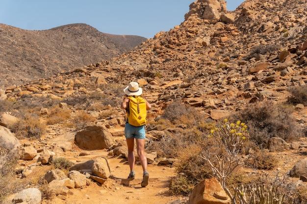 Caminhante com chapéu e mochila amarela percorrendo o caminho do desfiladeiro em direção ao mirador de la peñitas, em fuerteventura, nas ilhas canárias. espanha