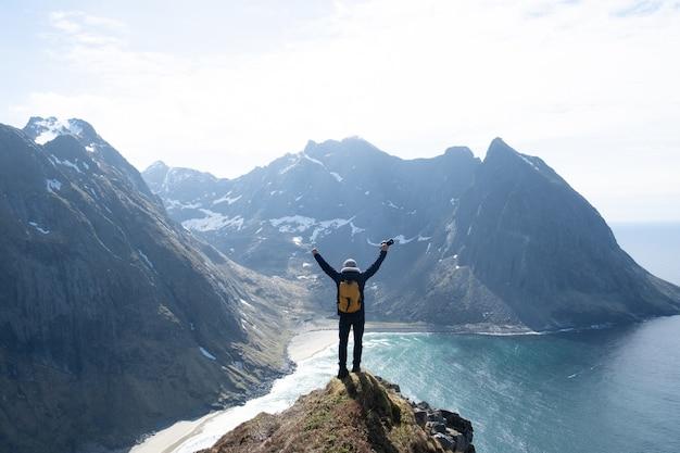 Caminhante com mochila apreciando a paisagem do pôr do sol em lofoten, noruega