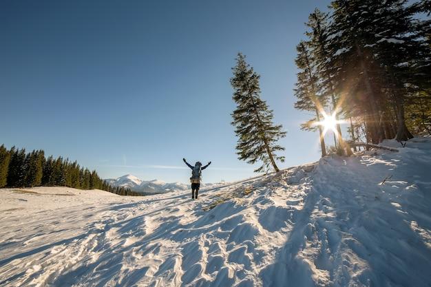 Caminhante com os braços erguidos em pé no inverno, apreciando a vista de neve ao longe