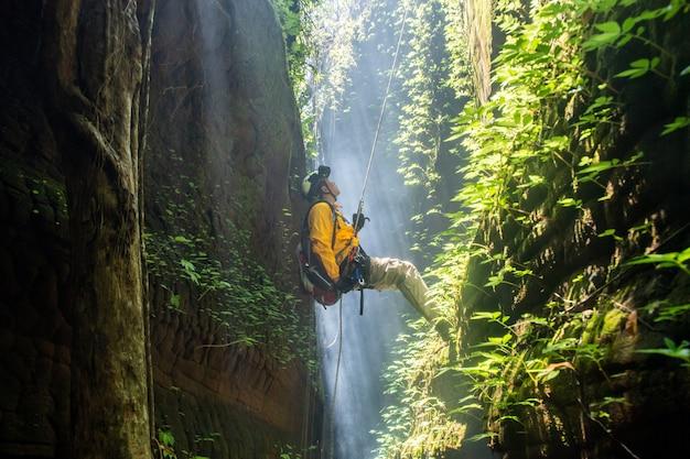 Caminhante de resgate com mochila escala a parede rochosa natural. usando mosquetão de corda para equipamento de escalada