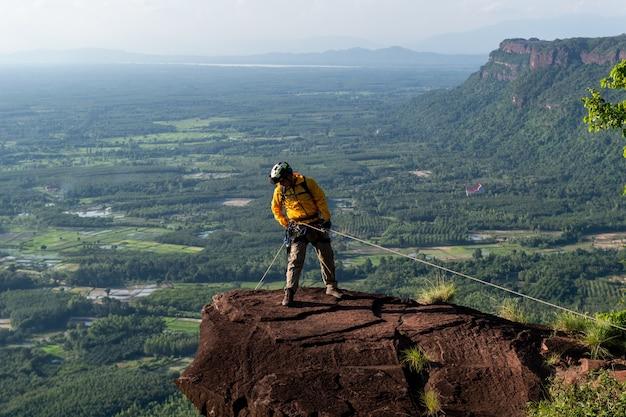 Caminhante de resgate com mochila escala a parede rochosa natural. usando mosquetão de corda para equipamento de escalada Foto Premium