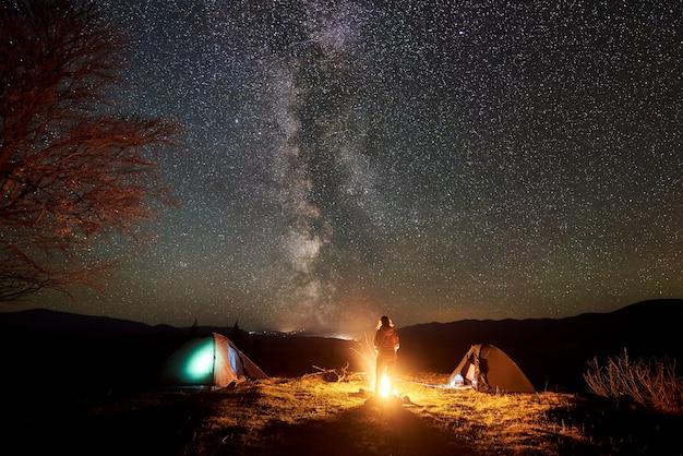 Caminhante descansando perto da fogueira sob o céu estrelado