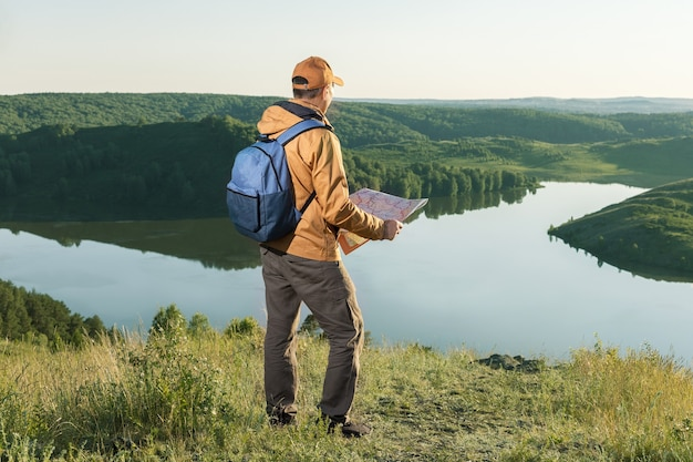 Caminhante do homem usando um mapa para localizar o destino. viagem, caminhadas, conceito de possibilidades infinitas.