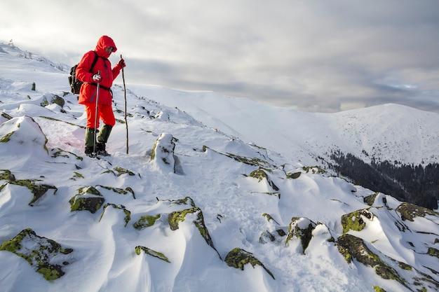 Caminhante do turista em roupas vermelhas brilhantes com bengalas descendo a encosta da montanha rochosa perigosa coberta de neve no fundo do espaço da cópia do céu nublado tempestuoso.