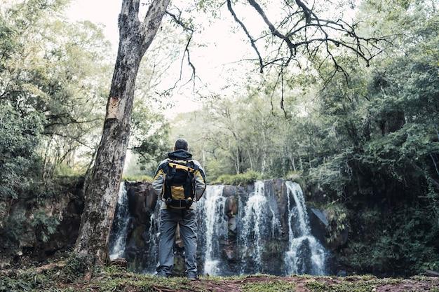 Caminhante em frente a uma cachoeira com mochila.