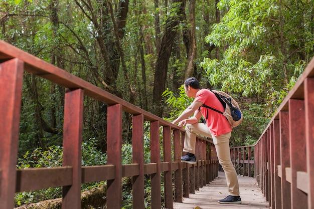 Caminhante em uma ponte velha na selva