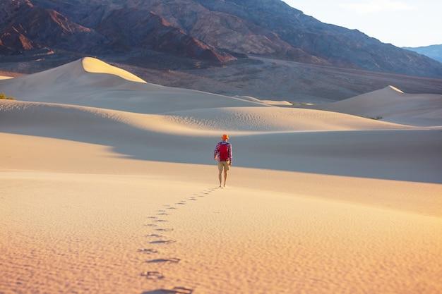 Caminhante entre dunas de areia no deserto