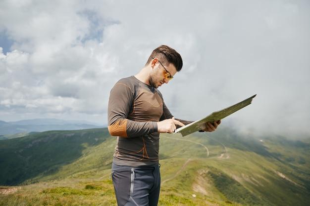 Caminhante esportivo parado com mapa na trilha da montanha