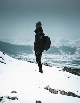 Caminhante legal em uma máscara e roupas escuras em pé sozinho em uma colina íngreme e nevada nas montanhas