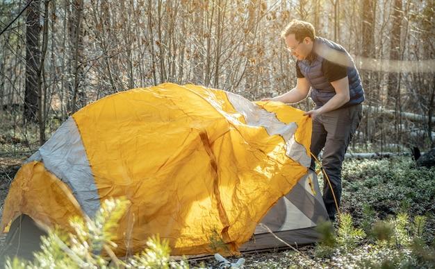 Caminhante masculino está montando uma tenda laranja brilhante na floresta. conceito de turismo, caminhadas e permanência na natureza.