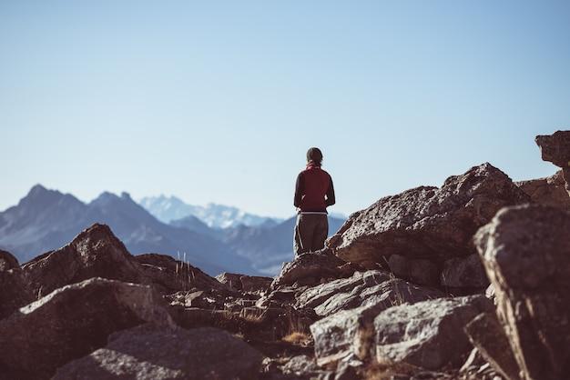 Caminhante na paisagem da montanha rochosa da alta altitude. aventuras de verão nos alpes franceses italianos,