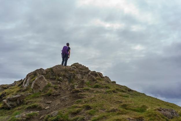 Caminhante no pico da montanha em the storr trail, ilha de skye, escócia