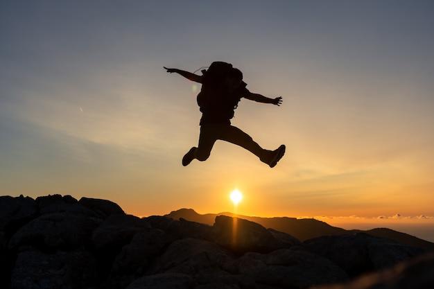 Caminhante no topo de uma montanha pulando sobre o sol ao pôr do sol, carregando uma mochila grande