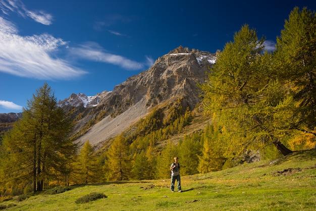 Caminhante que anda em um vale colorido com grande vista panorâmica e cores vívidas.