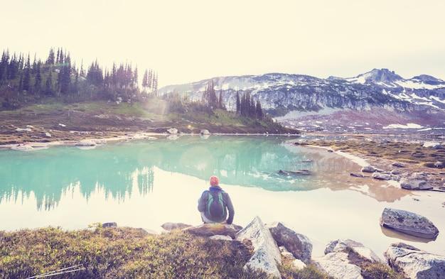 Caminhante relaxando em um lago sereno na montanha