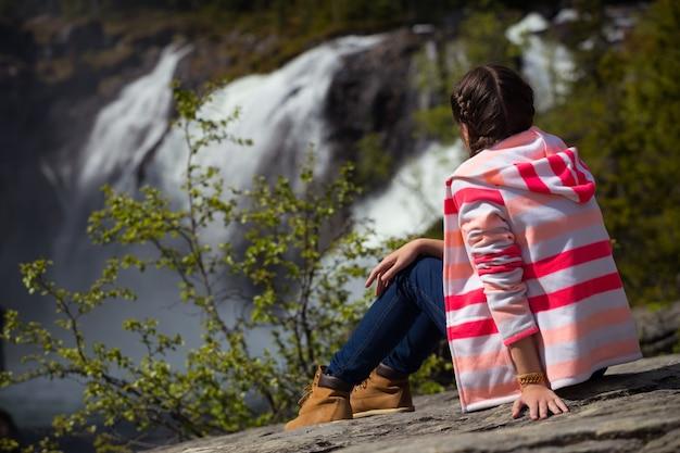 Caminhante sentada em uma rocha e em uma cachoeira rjukandefossen ao fundo, noruega