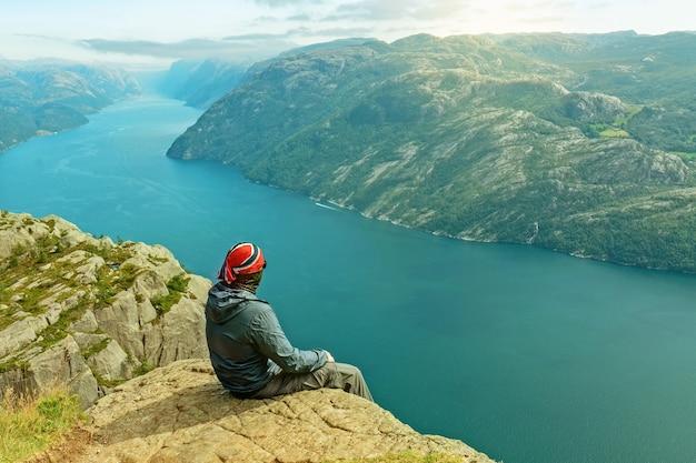 Caminhante sentado na rocha, paisagem marinha da montanha lysefjord, noruega.