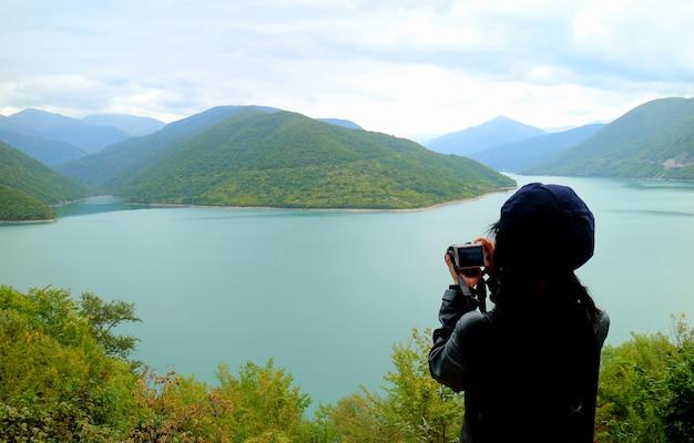 Caminhante tirando foto do reservatório de água jinvali, rio aragvi, geórgia